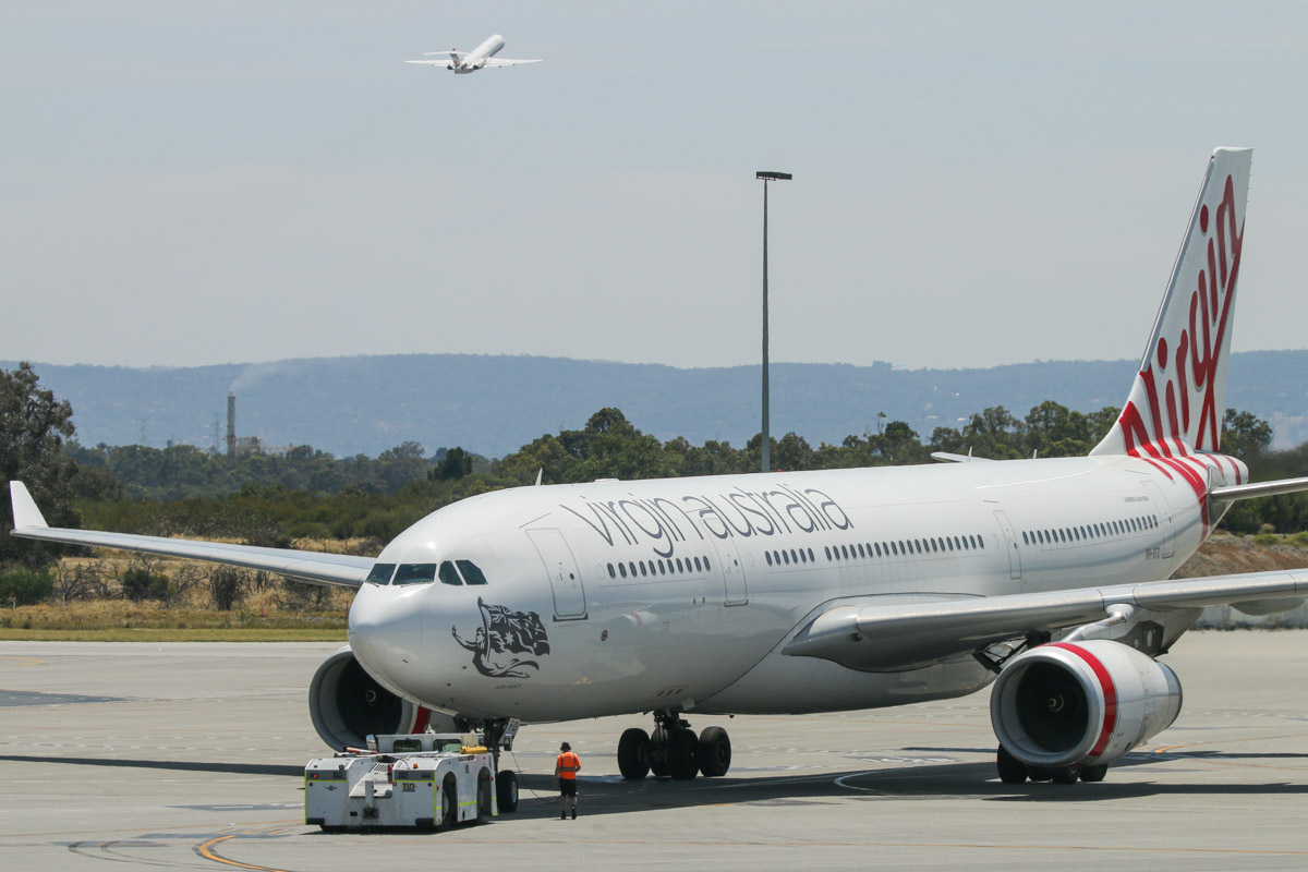 VH-XFD Airbus A330-243 (MSN 1306) of Virgin Australia, named 'Bells Beach', at Terminal 1 Domestic on the first day of operations, Perth Airport - Sun 22 November 2015. The first Airbus A330 to depart from the new terminal, operating flight VA556 to Sydney, pushing back from Bay 150 at 10:53am. In the background, climbing after take-off from runway 06 is VH-FSQ Fokker 100 (MSN 11450), named 'Bill's Bay', of Virgin Australia Regional Airlines, which was the first Fokker 100 to depart from the new terminal - operating flight VA1483 to Broome. Photo © David Eyre