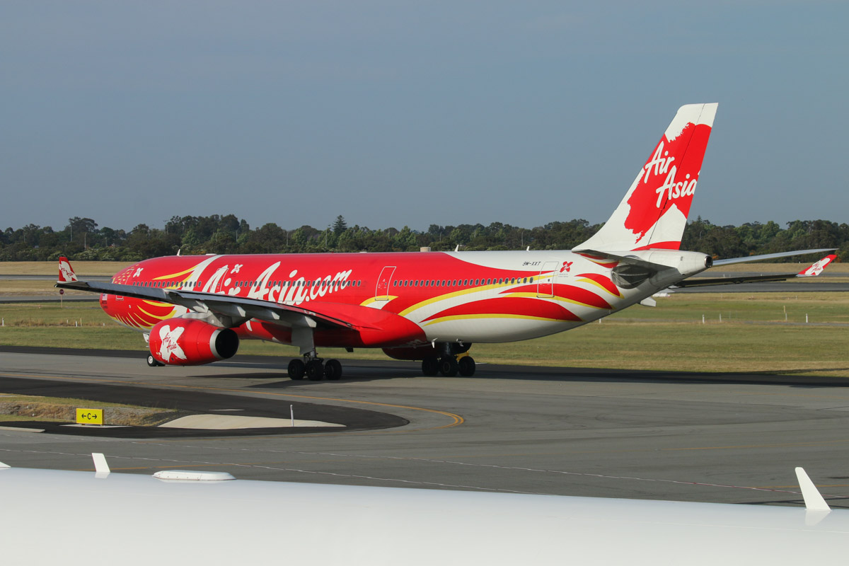 "9M-XXT Airbus A330-343X (MSN 1549) of AirAsia X, in special ""Xcintillating PhoeniX"" livery, seen from windows to the left of Gate 47A/Bay 147, Terminal 1 Domestic, Perth Airport - Sun 22 November 2015. Taxying along taxiway C to runway 03 at 7:08am as D7237 to Kuala Lumpur. Photo © David Eyre"