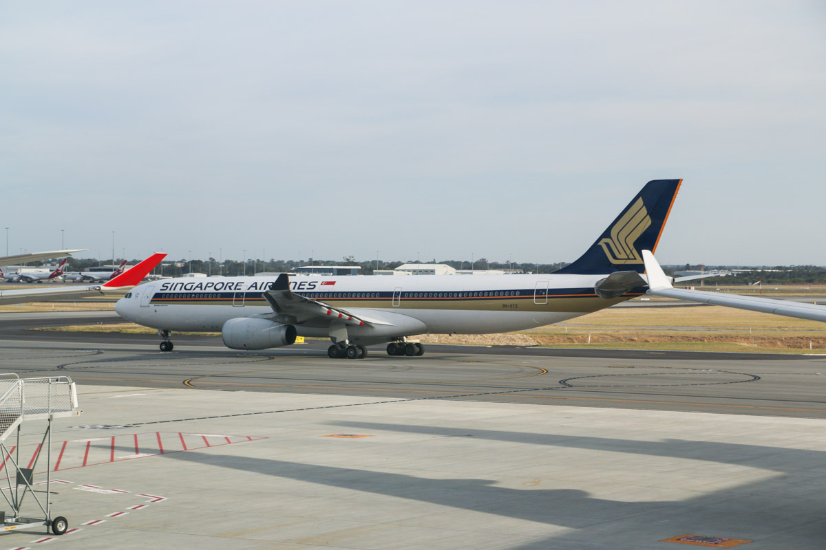 9V-STZ Airbus A330-343X (MSN 1477) of Singapore Airlines, seen from food court windows near Gate 50/Bay 150, Terminal 1 Domestic, Perth Airport - Sun 22 November 2015. Taxying out along taxiway T at 6:39am as SQ224 to Singapore. Note that if A330s are parked at Bay 149 (left) and Bay 150 (right), the wingtips get in the way with larger aircraft. Photo © David Eyre
