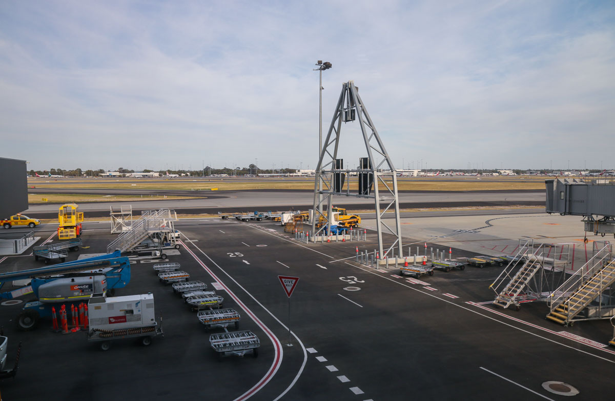 View west across runways and taxiways from the windows between Gate 47B/Bay 147 and Gate 48A/Bay 148, Terminal 1 Domestic, Perth Airport - Sun 22 November 2015. The large A-frame and light pole interrup the view, but it is possible to get photos either side of it. Photo © David Eyre