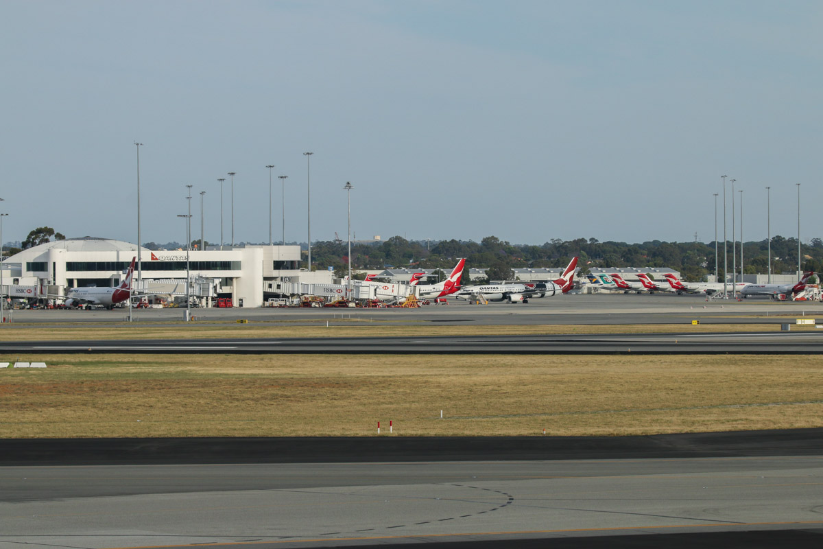 Qantas Domestic Terminal 4, seen from right of Gate 47B, Terminal 1 Domestic, Perth Airport - Sun 22 November 2015. VH-XZJ Boeing 737-838 (MSN 39365/4669) of Qantas, in 'Mendoowoorrji' Aboriginal art livery, is visible on the apron. Photo © David Eyre