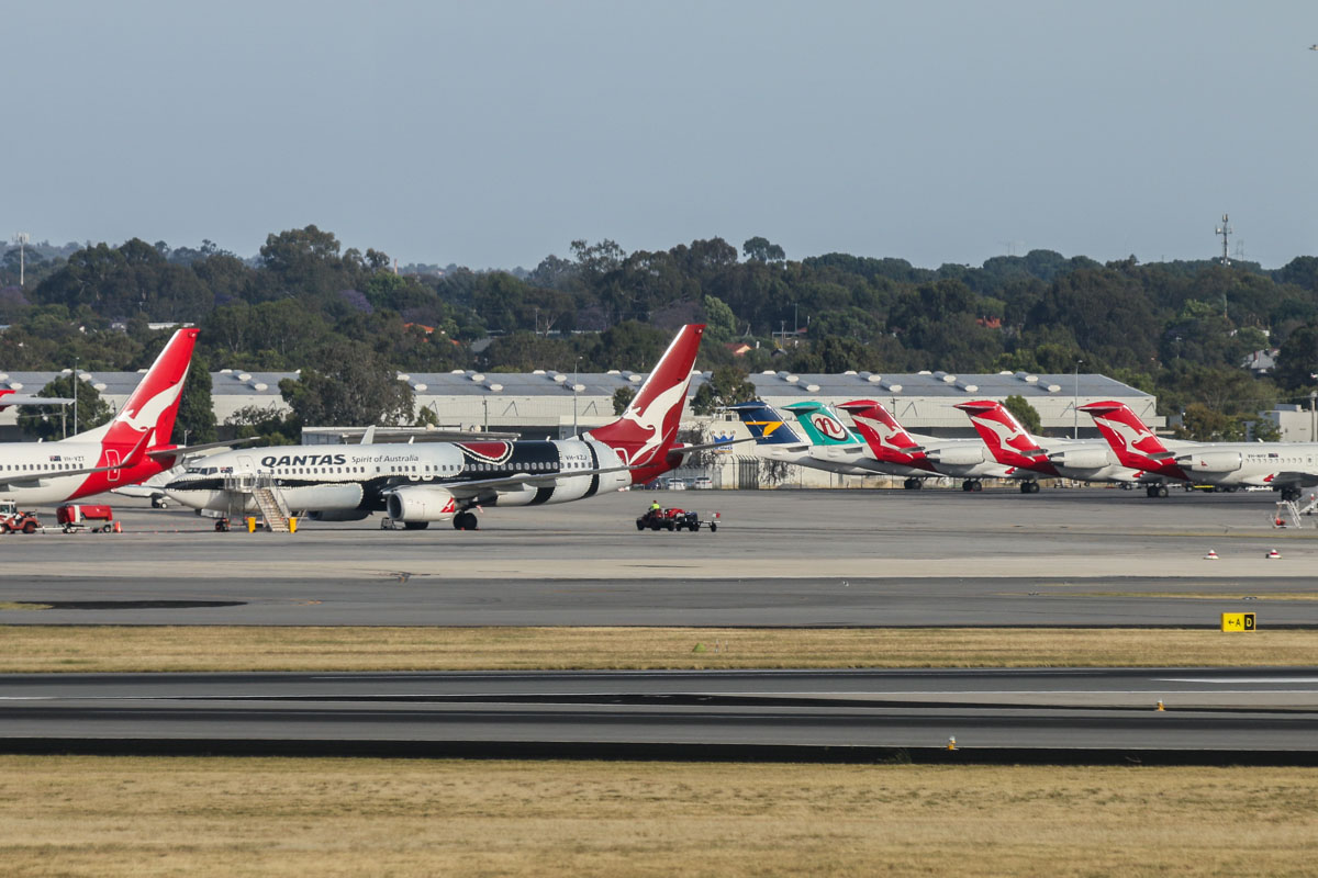 Qantas Domestic Terminal 4 and GA apron, seen from right of Gate 47B, Terminal 1 Domestic, Perth Airport - Sun 22 November 2015. VH-XZJ Boeing 737-838 (MSN 39365/4669) of Qantas, in 'Mendoowoorrji' Aboriginal art livery is visible on the apron, along with Fokker 100s of Alliance Airlines and Network Aviation (one in Network livery and he other three in QantasLink livery). Photo © David Eyre