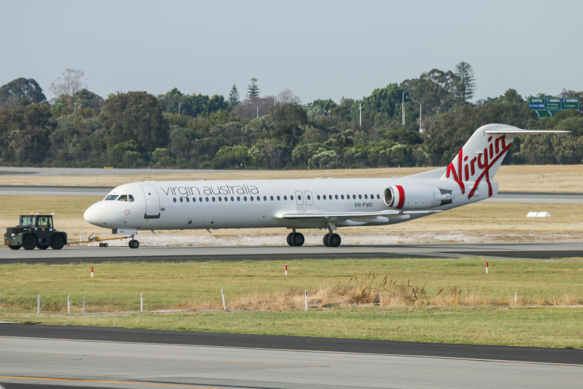 VH-FWI Fokker 100 (MSN 11318) of Virgin Australia Regional Airlines, seen from windows to the left of Gate 47A, Terminal 1 Domestic, Perth Airport - Sun 22 November 2015. Being towed east along taxiway C6 to Terminal 2 at 6:57am. Photo © David Eyre