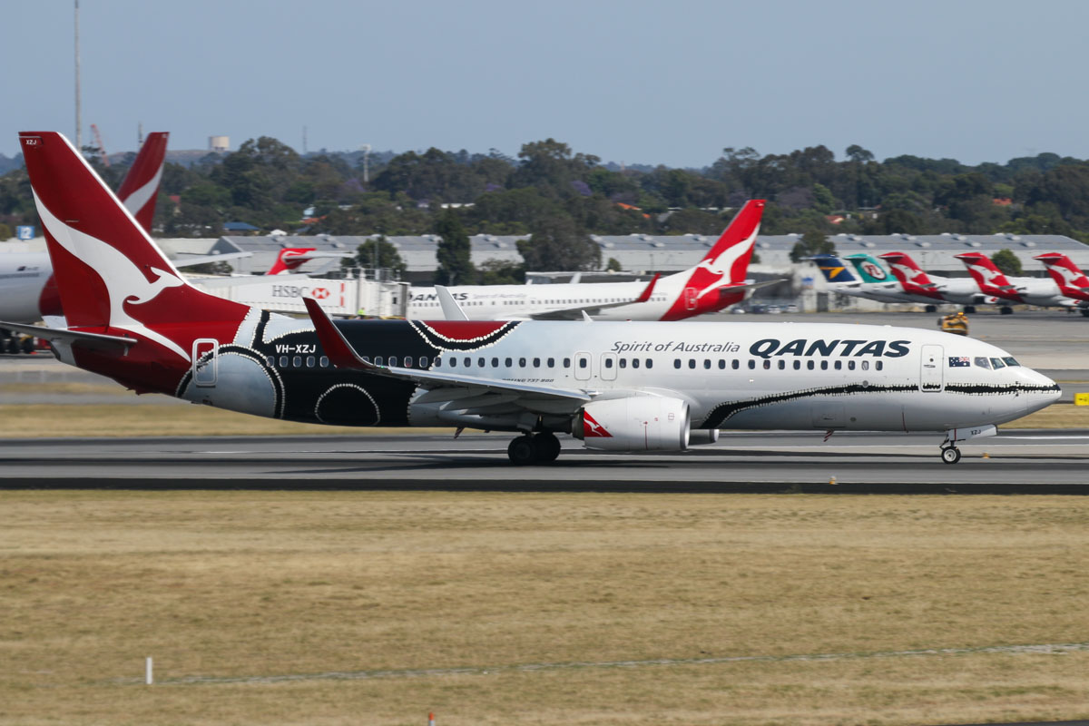 VH-XZJ Boeing 737-838 (MSN 39365/4669) of Qantas, in 'Mendoowoorrji' Aboriginal art livery, seen from right of Gate 47B, Terminal 1 Domestic, Perth Airport - Sun 22 November 2015. Taking off from runway 06 at 8:43am as QF792 to Darwin. Qantas Domestic Terminal 4 apron in the background. Photo © David Eyre