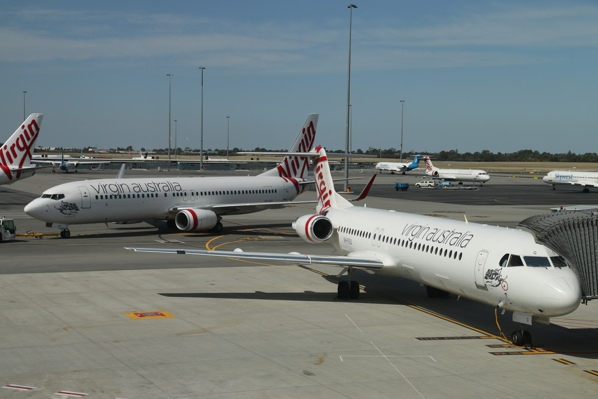 VH-FSQ Fokker 100 (MSN 11450), named 'Bill's Bay', of Virgin Australia Regional Airlines, at Gate 44/Bay 144, Terminal 1 Domestic on the first day of operations, Perth Airport - Sun 22 November 2015. Behind it is VH-VUV Boeing 737-8FE (MSN 34015/1594) of Virgin Australia, named 'Binalong Bay', pushing back from Gate 43/Bay 143. Photo © David Eyre
