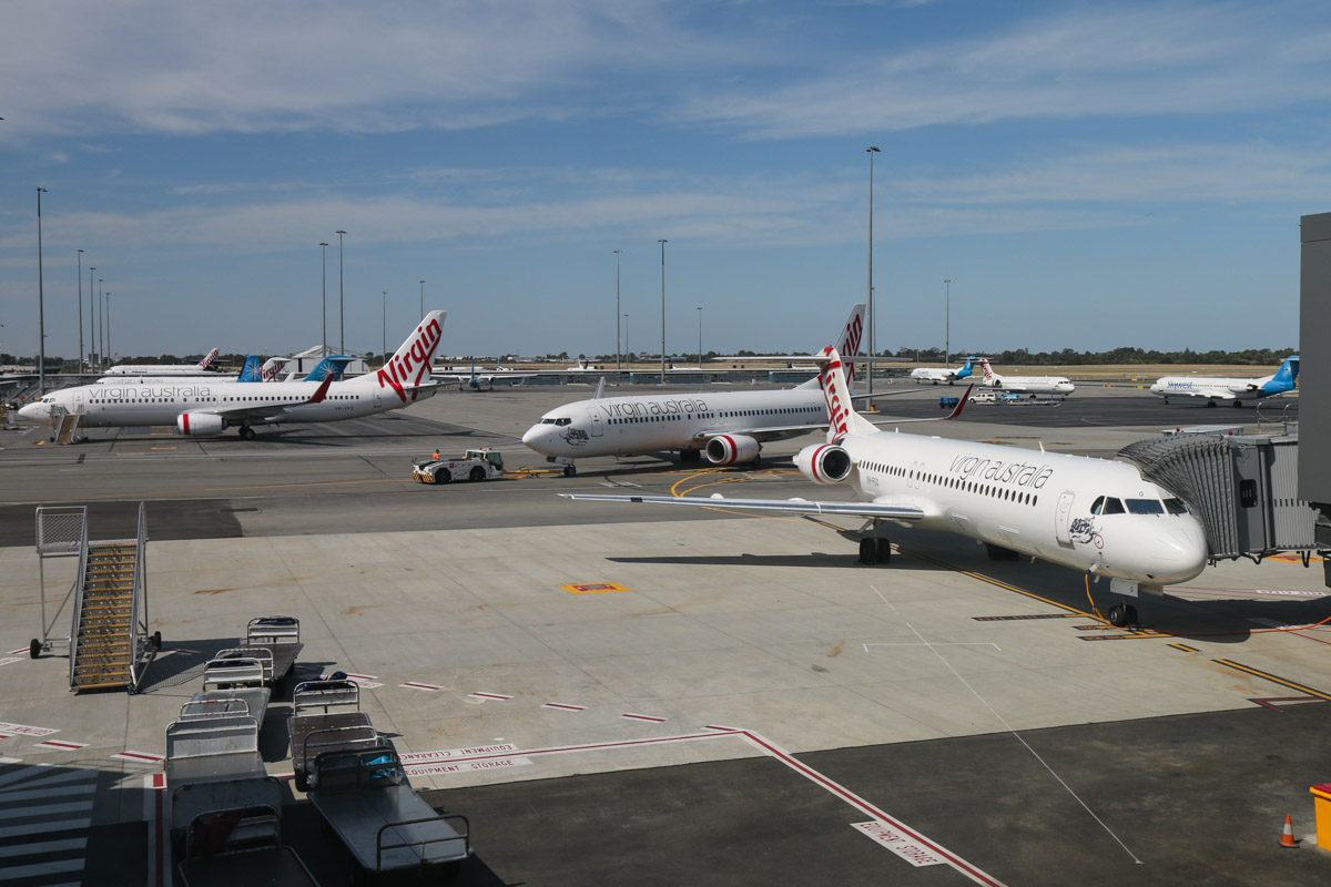 "VH-FSQ Fokker 100 (MSN 11450), named 'Bill's Bay', of Virgin Australia Regional Airlines, at Gate 44/Bay 144, Terminal 1 Domestic on the first day of operations, Perth Airport - Sun 22 November 2015. Behind it is VH-VUV Boeing 737-8FE (MSN 34015/1594) of Virgin Australia, named 'Binalong Bay', pushing back from Gate 43/Bay 143. On the left, parked at Bay 201 is VH-YFQ Boeing 737-8FE (MSN 41010/4494) of Virgin Australia, named ""Whiting Beach"". Photo © David Eyre"