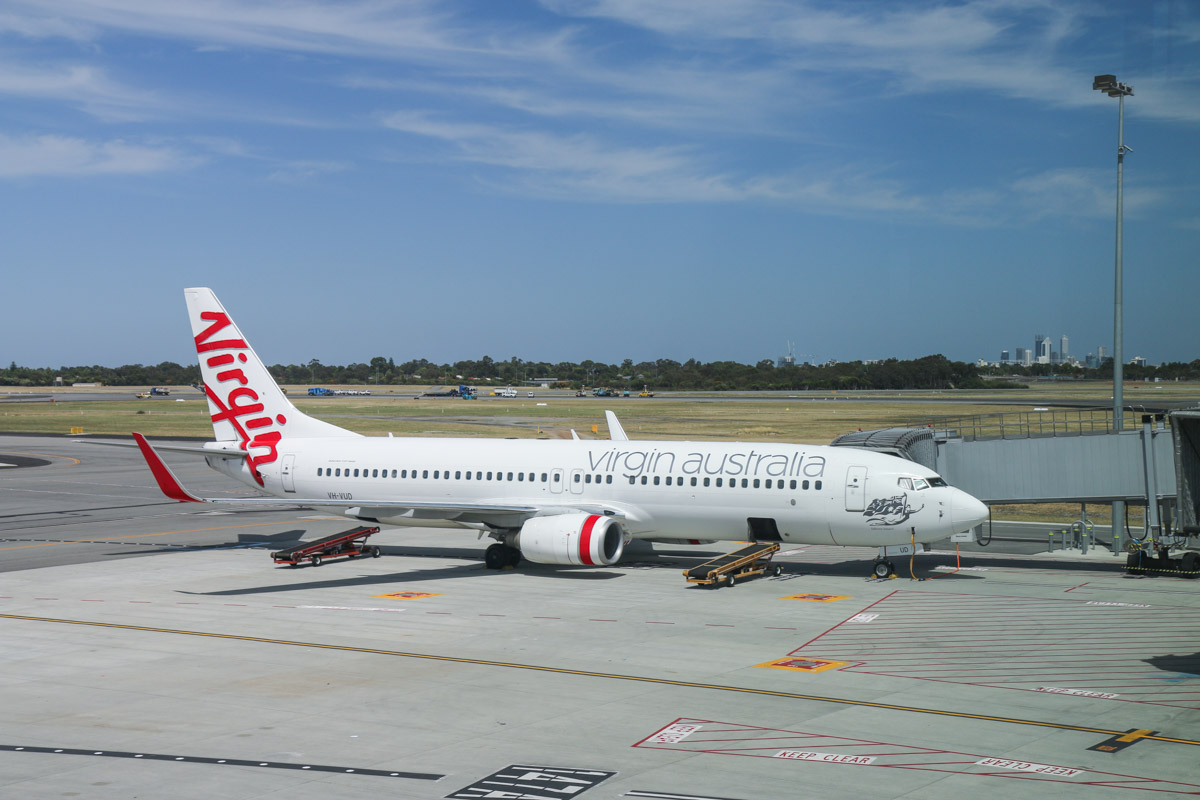 VH-VUD Boeing 737-8FE (MSN 34015/1594) of Virgin Australia, named 'Tallows Beach', at Bay 147B, Terminal 1 Domestic on the first day of operations, Perth Airport - Sun 22 November 2015. The city of Perth can be seen in the distance, on the right. Construction vehicles are on runway 03/21 behind the 737. Photo © David Eyre