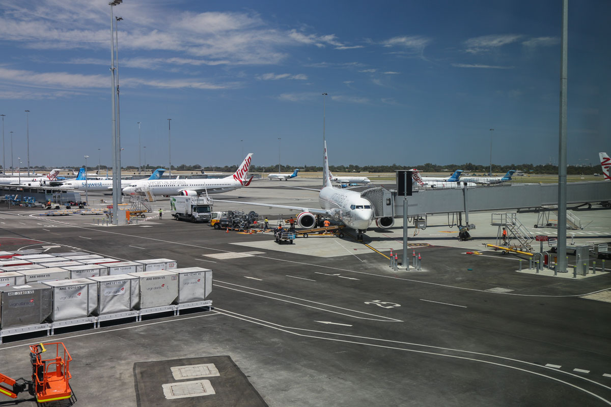 Gate 43/Bay 143 and Terminal 2 apron, seen from near the moving walkway at the east end of Terminal 1 Domestic pier, on the first day of operations, Perth Airport - Sun 22 November 2015. Parked at Gate 43/Bay 143 nearest the camera is VH-VUF Boeing 737-8FE (MSN 34168/1697), named 'Hobart Honey', of Virgin Australia. To the left is VH-YFQ (MSN 41010/4494), named 'Whiting Beach'. Photo © David Eyre