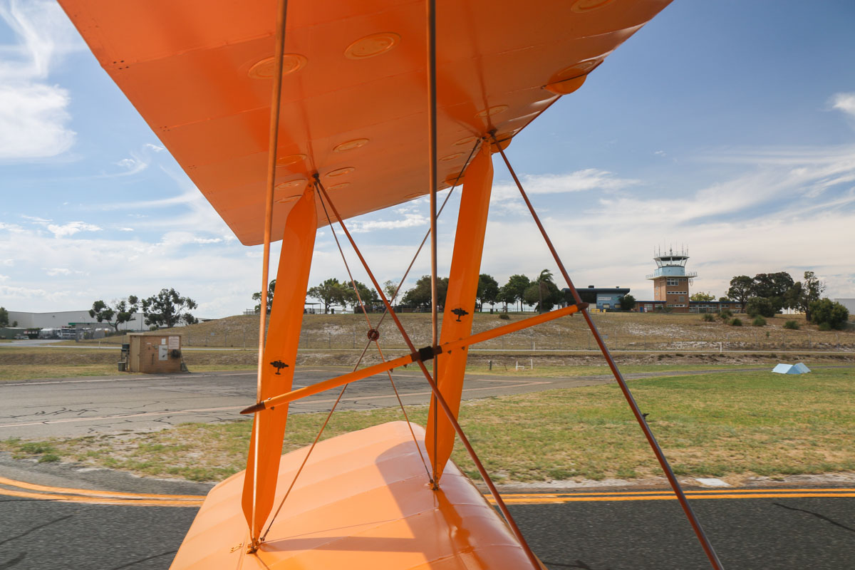 View from VH-BTP / A17-744 De Havilland DH-82A Tiger Moth (MSN DHA1075/T315) owned by Clark Rees, at Jandakot Airport - Tue 26 January 2016 - Australia Day Air Show. Taxying out at 3:32pm to runway 24R for take-off. Spectator area, Aviators Cafe and the control tower are visible on our left. Photo © David Eyre