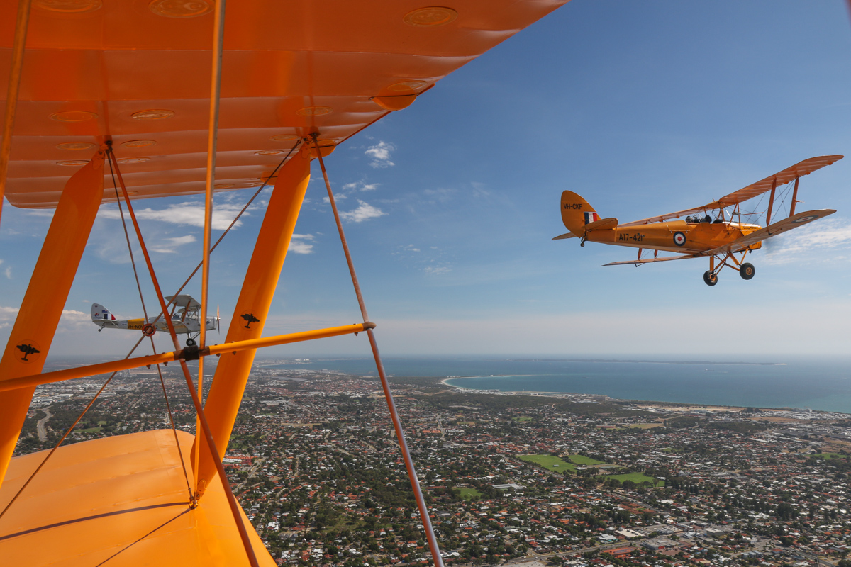 De Havilland DH-82A Tiger Moths: VH-NOV (MSN DHA1088) flown by Barry Markham and VH-CKF/A17-421 (MSN DHA596/T200) flown by Trevor Jones, over O'Connor - Tue 26 January 2016 - Australia Day Air Show. Flying west. Point Peron, Woodman Point and Garden Island visible. Photo taken from VH-BTP / A17-744 De Havilland DH-82A Tiger Moth (MSN DHA1075/T315) owned by Clark Rees. Photo © David Eyre