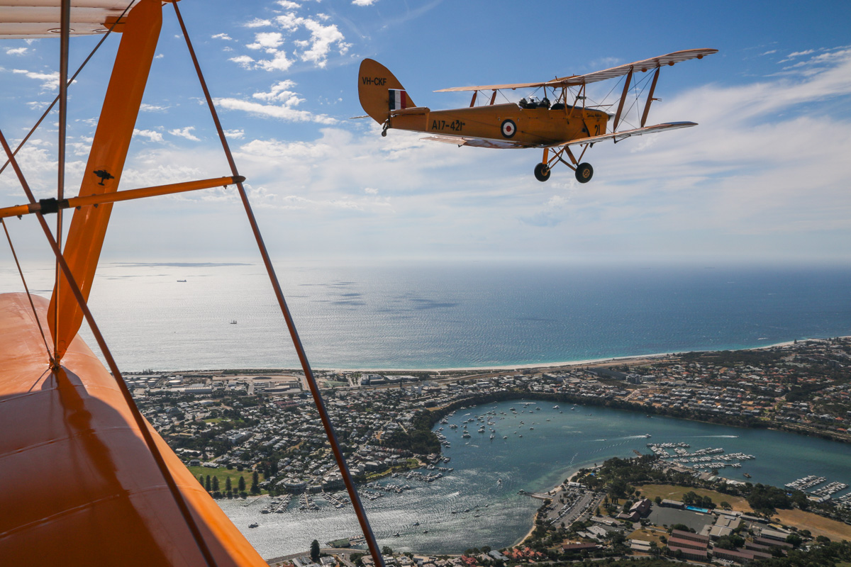VH-CKF/A17-421 De Havilland DH-82A Tiger Moth (MSN DHA596/T200) owned by the Royal Aero Club of Western Australia, flown by Trevor Jones, over East Fremantle, Tue 26 January 2016 - Australia Day Air Show. Visible in the distance is Rottnest Island, 18 kilometres offshore. Photo taken from VH-BTP / A17-744 De Havilland DH-82A Tiger Moth (MSN DHA1075/T315) owned by Clark Rees Photo © David Eyre