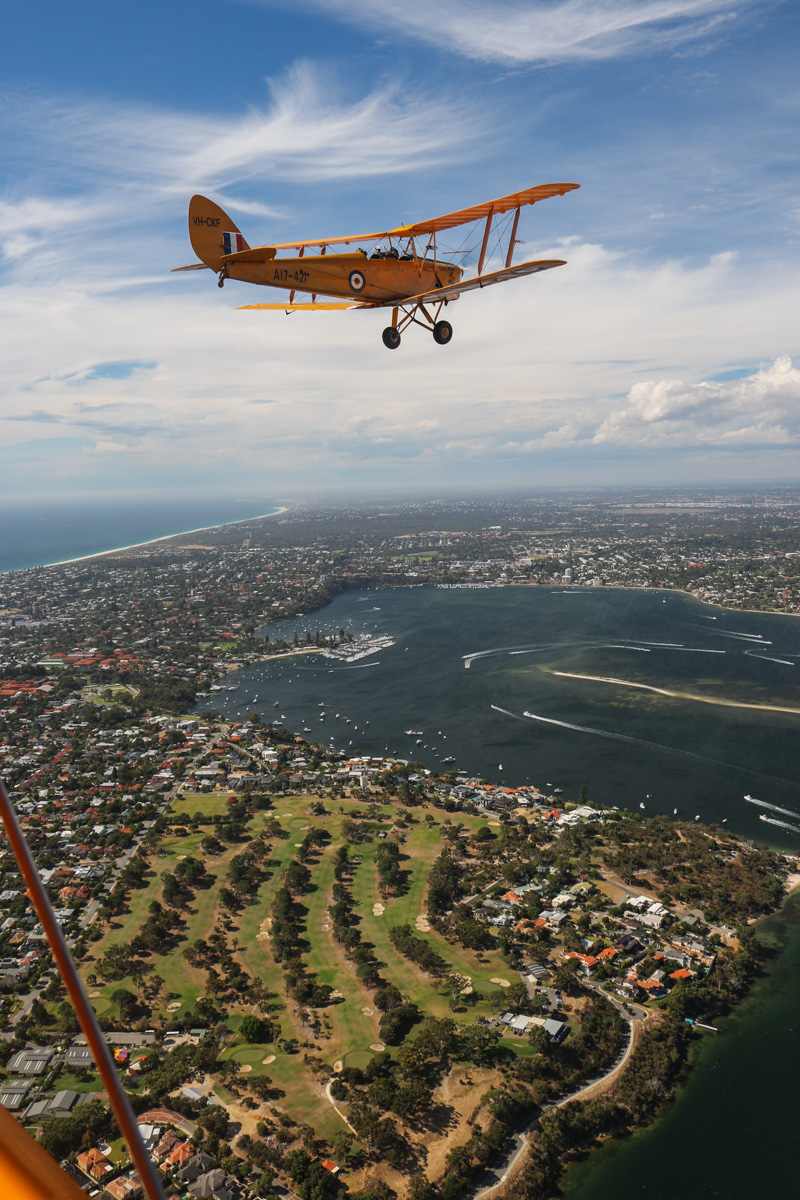 VH-CKF/A17-421 De Havilland DH-82A Tiger Moth (MSN DHA596/T200) owned by the Royal Aero Club of Western Australia, flown by Trevor Jones, over the Swan River at Mosman Park, Tue 26 January 2016 - Australia Day Air Show. View facing north towards Peppermint Grove and Claremont. Photo taken from VH-BTP / A17-744 De Havilland DH-82A Tiger Moth (MSN DHA1075/T315) flown by Clark Rees. Photo © David Eyre