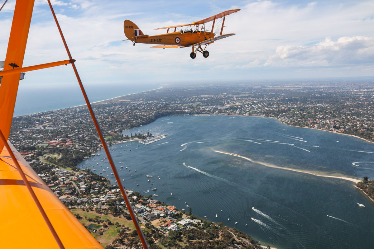 VH-CKF/A17-421 De Havilland DH-82A Tiger Moth (MSN DHA596/T200) owned by the Royal Aero Club of Western Australia, flown by Trevor Jones, over the Swan River at Mosman Park, Tue 26 January 2016 - Australia Day Air Show. View facing north towards Peppermint Grove and Claremont, with Point Walter on the lower right. Photo taken from VH-BTP / A17-744 De Havilland DH-82A Tiger Moth (MSN DHA1075/T315) owned by Clark Rees Photo © David Eyre
