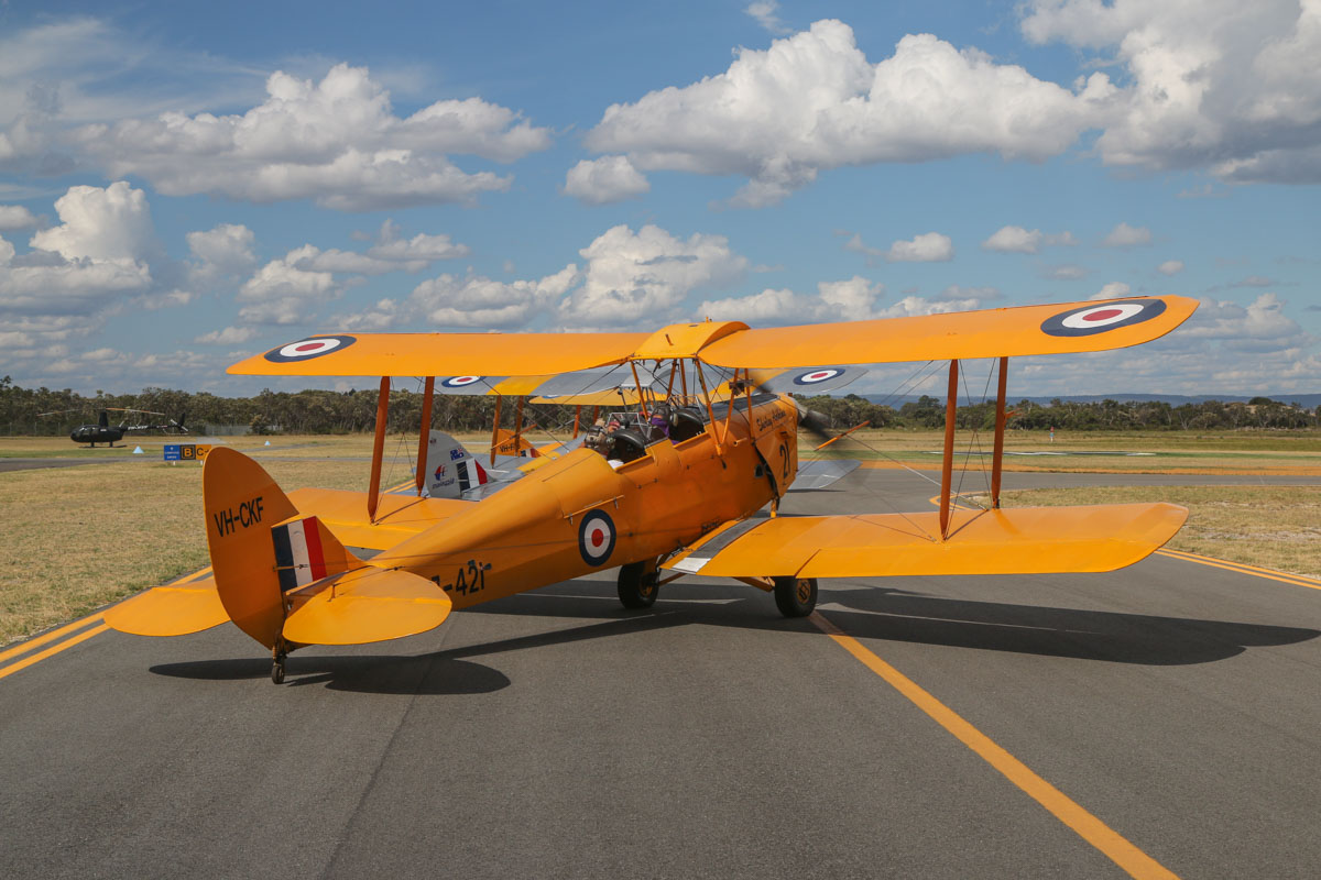 VH-CKF/A17-421 De Havilland DH-82A Tiger Moth (MSN DHA596/T200) owned by the Royal Aero Club of Western Australia Inc, flown by Trevor Jones , at Jandakot Airport - Tue 26 January 2016 - Australia Day Air Show. Holding on taxiway B near runway 24R, to do engine run-up checks before departure. Visible behind are two more Tiger Moths, VH-NOV, owned and flown by Barry Markham, and VH-FAS/A17-37 of the Royal Aero Club. VH-FAS suffered mechanical problems and had to taxi back, leaving VH-CKF to step up as formation leader. Photo taken from VH-BTP / A17-744 De Havilland DH-82A Tiger Moth (MSN DHA1075/T315) owned by Clark Rees Photo © David Eyre