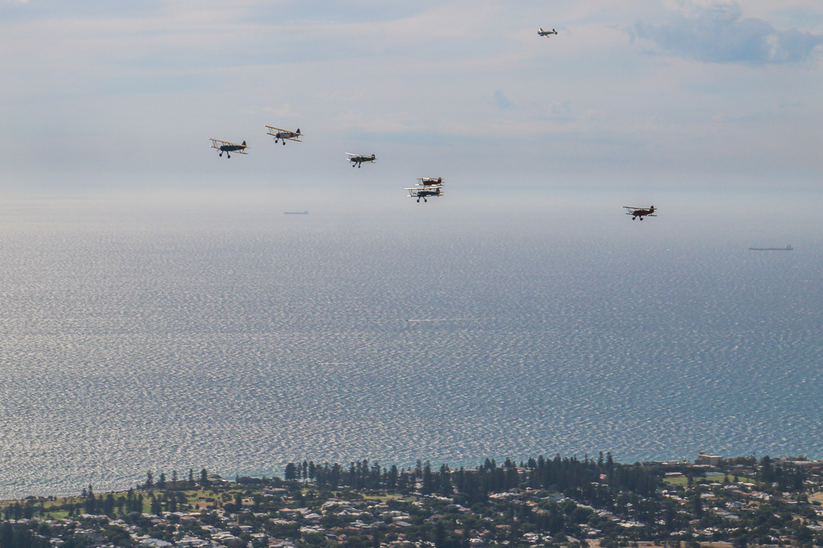 """The 'Oldtimers' formation, over Cottesloe, Tue 26 January 2016 - Australia Day Air Show. Fying south along the coast to join the rear of our formation. Boeing Stearmans VH-YDF / 4269 / 591, flown by Werner Buhlmann; VH-YND / """"42–755362 / 362"""" in US Navy markings, flown by Carl Ende; VH-URC in US Army Air Corps markings, flown by Rod Edwards; VH-KIL / """"14"""" CASA 1-131E Jungmann, in Japanese markings, flown by Bert Filippi; VH-WQW Great Lakes 2T-1A-2 Sport Trainer, flown by Franc Smit; VH-YRB WACO Aircraft YMF-F5C, flown by Archie Dudgeon; VH-FID Beech D.18S, flown by Stuart Adamson. Photo © David Eyre"""