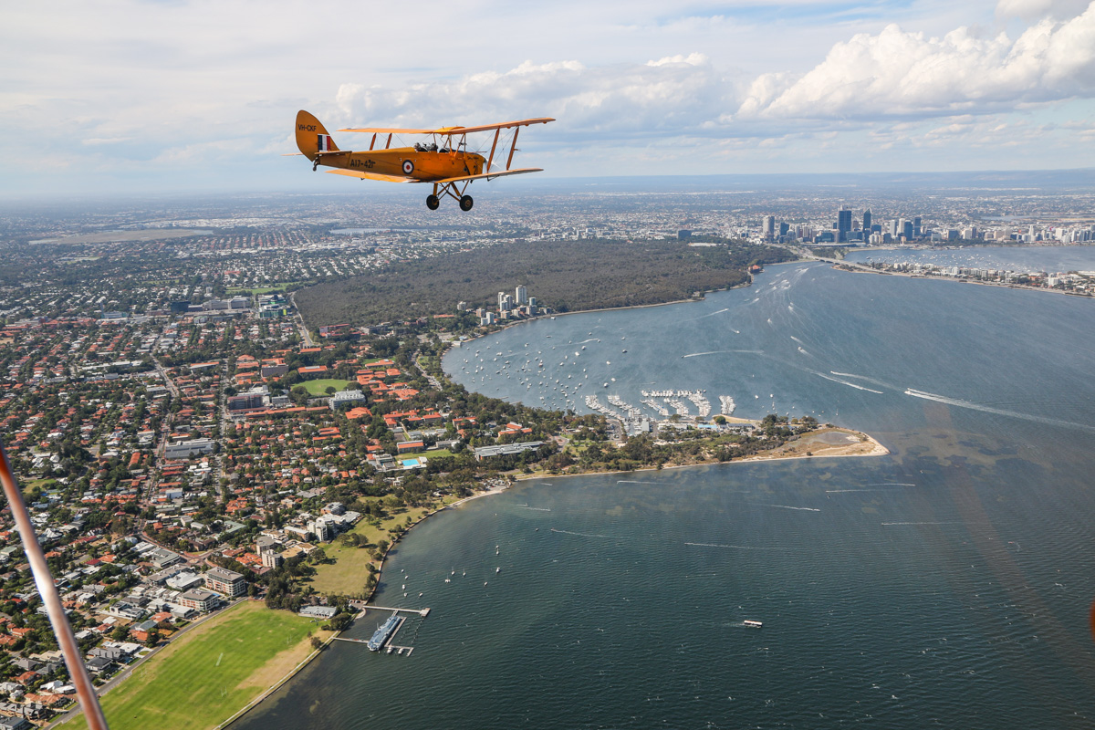 VH-CKF/A17-421 De Havilland DH-82A Tiger Moth (MSN DHA596/T200) owned by the Royal Aero Club of Western Australia, flown by Trevor Jones, over the Swan River at Nedlands, Tue 26 January 2016 - Australia Day Air Show. View facing northeast towards Perth city and Kings Park. Pelican Point in Crawley, now the home of Royal Perth Yacht Club, was formerly a World War Two seaplane base, used by Catalinas of the US Navy. Qantas also operated Catalinas from the southern side (directly below the propeller of VH-CKF in this photo, where a boat ramp and car park now stands), flying direct to Ceylon (Sri Lanka). Photo taken from VH-BTP / A17-744 De Havilland DH-82A Tiger Moth (MSN DHA1075/T315) flown by Clark Rees. Photo © David Eyre