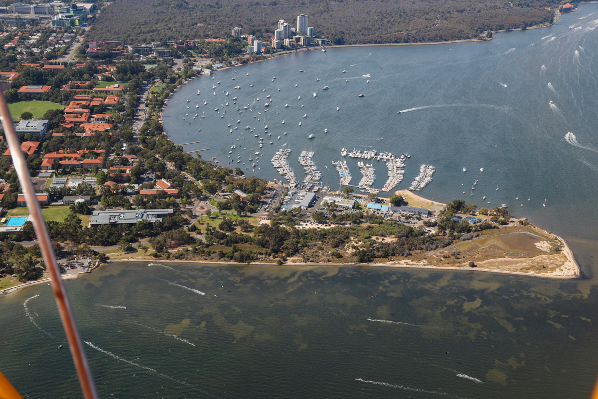 Former World War Two seaplane base at Pelican Point, Crawley, Tue 26 January 2016 - Australia Day Air Show. View facing northeast towards Kings Park. The current site of Royal Perth Yacht Club was formerly a World War Two seaplane base, used by Catalinas of the US Navy. Qantas also operated Catalinas from the southern side, where a boat ramp and car park are now located (near the strut in this photo). Qantas flew direct from the Swan River to Ceylon (Sri Lanka), a flight of up to 32 hours, which still holds the record for the longest regular passenger flight. Photo taken from VH-BTP / A17-744 De Havilland DH-82A Tiger Moth (MSN DHA1075/T315) flown by Clark Rees. Photo © David Eyre