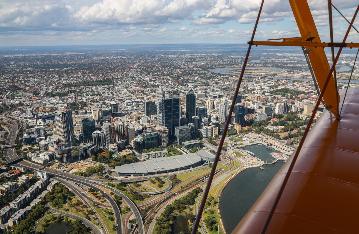 The city of Perth, seen from VH-BTP / A17-744 De Havilland DH-82A Tiger Moth (MSN DHA1075/T315) flown by Clark Rees, Tue 26 January 2016 - Australia Day Air Show. Seen off our right side, as we flew north. Mitchell Freeway on the left and the new Elizabeth Quay inlet can be seen on the right - it officially opened a few days later. Photo © David Eyre