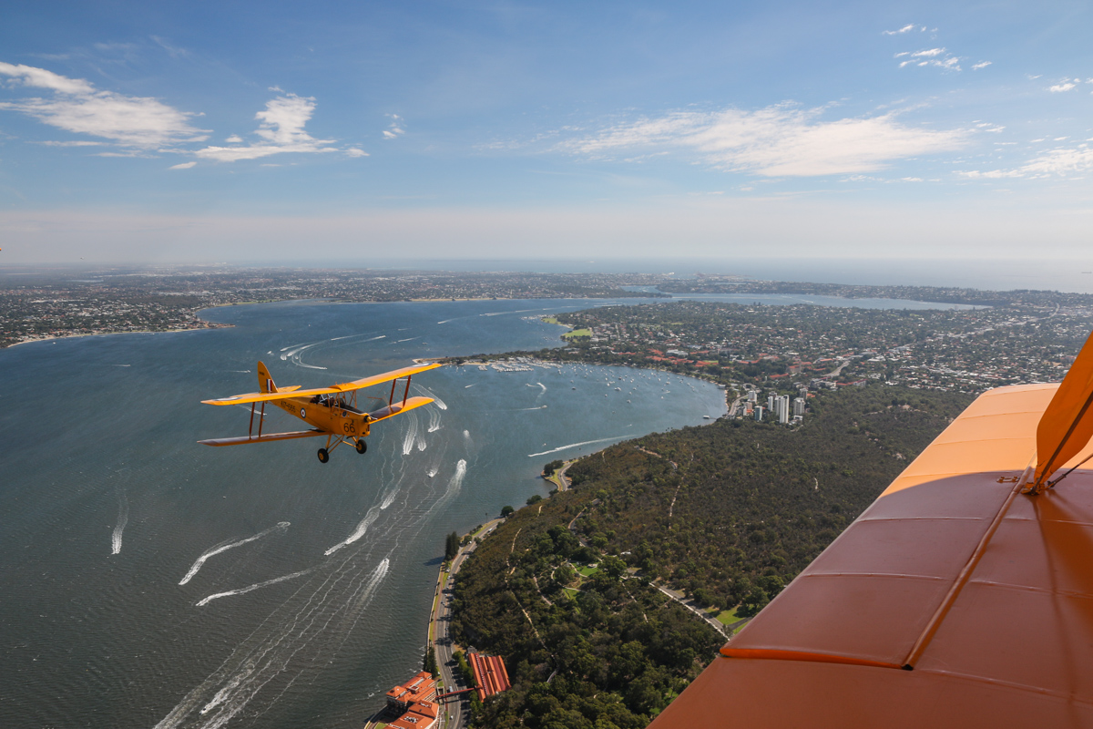 VH-BAR/A17-666 De Havilland DH-82A Tiger Moth (MSN DHA816/T342) flown by Kevin Bailey, over the Swan River near Kings Park, Tue 26 January 2016 - Australia Day Air Show. Pelican Point at Crawley is visible near the left wing of VH-BAR. This was a former World War Two seaplane base, used by Catalina flying boats of the US Navy. Photo taken from VH-BTP / A17-744 De Havilland DH-82A Tiger Moth (MSN DHA1075/T315) owned by Clark Rees. Photo © David Eyre