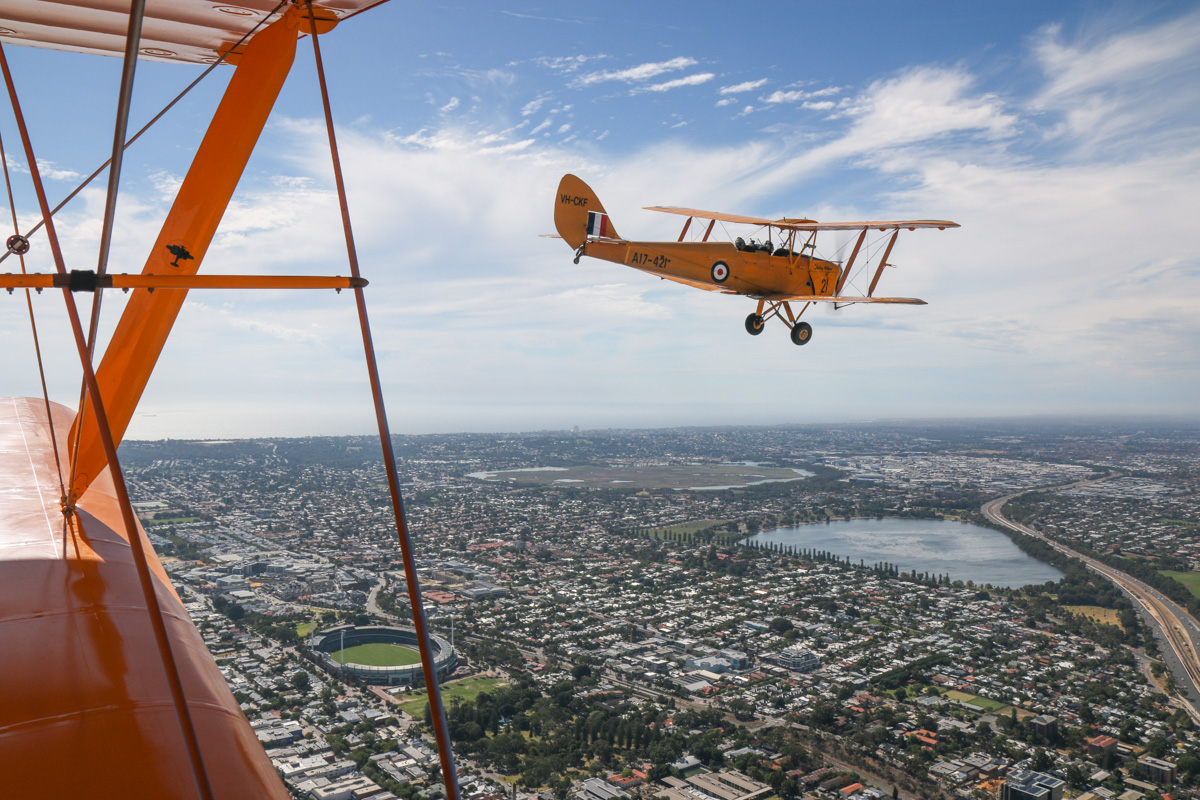 VH-CKF/A17-421 De Havilland DH-82A Tiger Moth (MSN DHA596/T200) owned by the Royal Aero Club of Western Australia, flown by Trevor Jones, over Subiaco, Tue 26 January 2016 - Australia Day Air Show. View facing northwest towards Domain Stadium (Subiaco Oval football ground), with Lake Monger on the right and Herdsman Lake in the centre. Photo taken from VH-BTP / A17-744 De Havilland DH-82A Tiger Moth (MSN DHA1075/T315) flown by Clark Rees. Photo © David Eyre