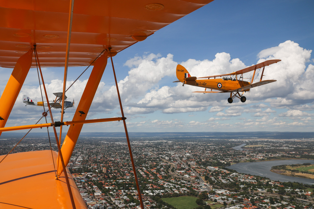 De Havilland DH-82A Tiger Moths: VH-NOV (MSN DHA1088) flown by Barry Markham and VH-CKF/A17-421 (MSN DHA596/T200), flown by Trevor Jones, over Northbridge, Tue 26 January 2016 - Australia Day Air Show. Heading southeast towards Swan River. Perth Airport visible in the distance on the right. Photo taken from VH-BTP / A17-744 De Havilland DH-82A Tiger Moth (MSN DHA1075/T315) flown by Clark Rees. Photo © David Eyre