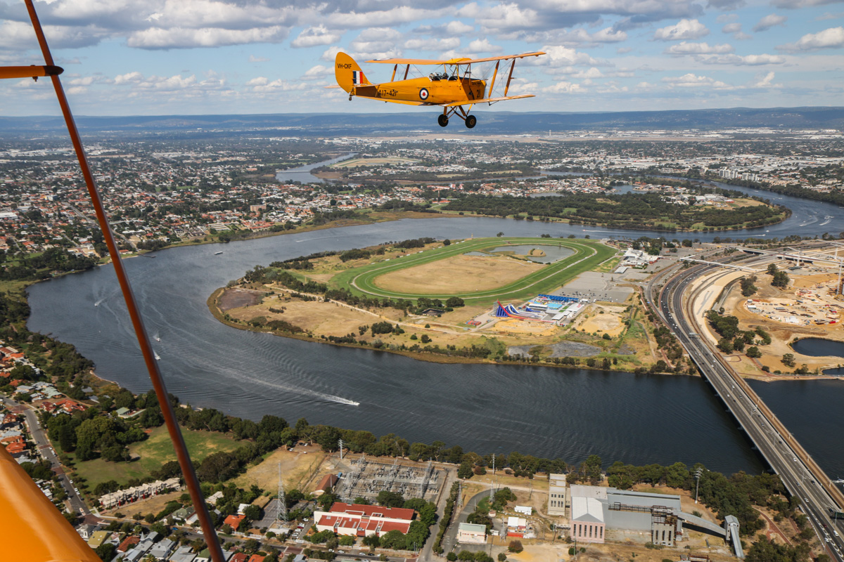 VH-CKF/A17-421 De Havilland DH-82A Tiger Moth (MSN DHA596/T200), flown by Trevor Jones, over East Perth, Tue 26 January 2016 - Australia Day Air Show. About to turn right to commence the flypast. The green oval horse racing track of Belmont Park Racecourse is visible - in January 1911, this was the site of the first aeroplane flights in Western Australia, by New Zealander, Joseph Joel Hammond in a Bristol Boxkite. Norman Brearley based his two Avro 504J aircraft in a hangar located between the track and the river in 1919, and used it as an airstrip before moving to Langley Park. Beyond Belmont Park is the former Maylands Aerodrome on Maylands Peninsula, which still has its aircraft hangars - it was Perth's first official airport and operated from January 1924 to June 1963. Perth Airport is visible in the distance. Photo taken from VH-BTP / A17-744 De Havilland DH-82A Tiger Moth (MSN DHA1075/T315) flown by Clark Rees. Photo © David Eyre
