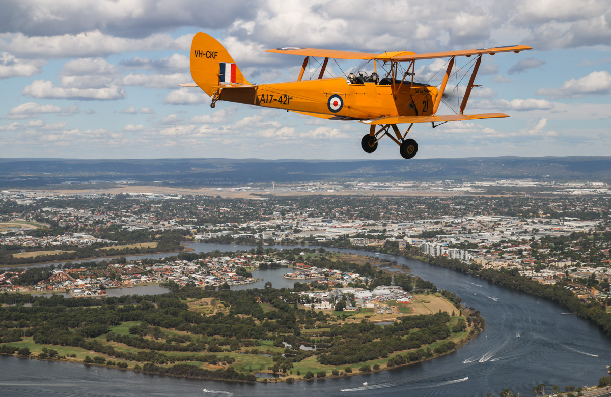 VH-CKF/A17-421 De Havilland DH-82A Tiger Moth (MSN DHA596/T200), flown by Trevor Jones, over East Perth, Tue 26 January 2016 - Australia Day Air Show. About to turn right to commence the flypast. Visible on the right side of Maylands Peninsula is the former Maylands Aerodrome, which still has its aircraft hangars. It was Perth's first official airport and operated from January 1924 to June 1963. Perth Airport is visible in the distance. Photo taken from VH-BTP / A17-744 De Havilland DH-82A Tiger Moth (MSN DHA1075/T315) flown by Clark Rees. VH-CKF (then VH-CAG) flew from Maylands during 1949-65 and VH-BTP was based there from 1958-62. Photo © David Eyre