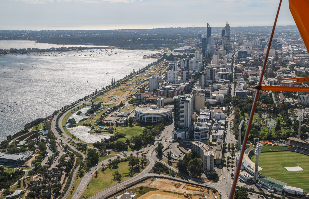 Perth city, East Perth, and South Perth, seen from VH-BTP / A17-744 De Havilland DH-82A Tiger Moth (MSN DHA1075/T315) flown by Clark Rees, over East Perth, Tue 26 January 2016 - Australia Day Air Show. At bottom right is the WACA cricket ground - in 1919 Norman Brearley flew joyflights from there in his Avro 504J biplane. Later that year, he moved his base from Belmont Park Racecourse to what is now the west end of Langley Park, Langley Park is visible to the left of the city. Photo © David Eyre