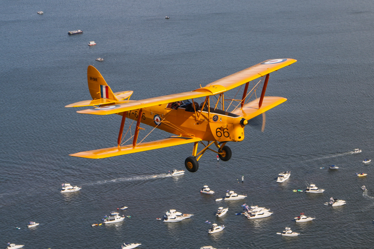 VH-BAR/A17-666 De Havilland DH-82A Tiger Moth (MSN DHA816/T342) flown by Kevin Bailey, over the Swan River near South Perth - Tue 26 January 2016 - Australia Day Air Show. Flying towards the Narrows Bridge. The fireworks barges for Skyworks are lined up to the upper left of the tail of VH-BAR. Below the aircraft are a number of boats flying the Australian flag, watching the air show and later, the fireworks display. Photo © David Eyre