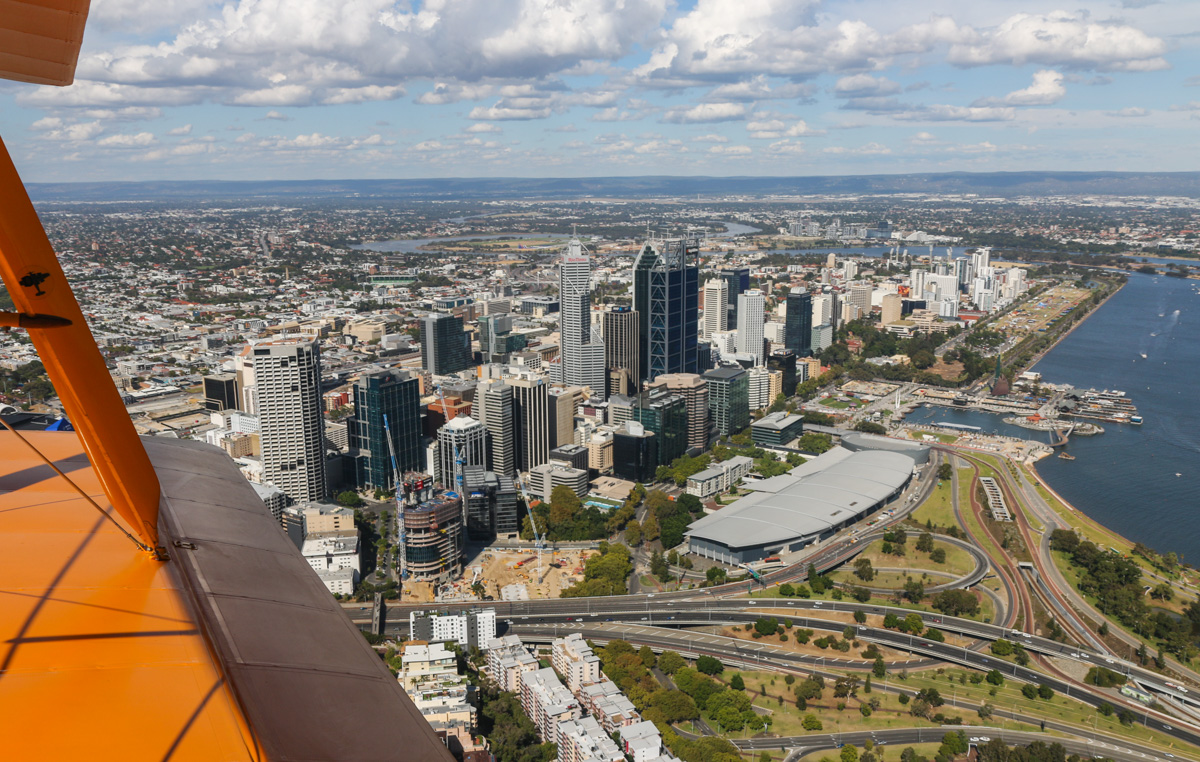 Perth city, seen from VH-BTP / A17-744 De Havilland DH-82A Tiger Moth (MSN DHA1075/T315) flown by Clark Rees, over Kings Park, Tue 26 January 2016 - Australia Day Air Show. The newly completed inlet at Elizabeth Quay was officially opened three days after this photo, on 29 January 2016. The former unofficial airport at Langley Park is visible at centre right and in the distance is Perth Airport. Photo © David Eyre