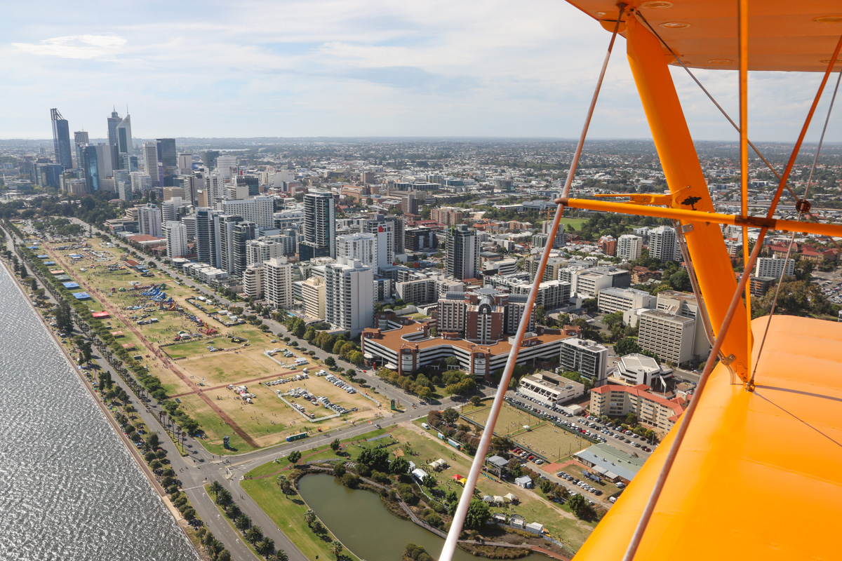 Perth city, East Perth, and Langley Park, seen from VH-BTP / A17-744 De Havilland DH-82A Tiger Moth (MSN DHA1075/T315) flown by Clark Rees, over the Swan River at East Perth, Tue 26 January 2016 - Australia Day Air Show. In 1919, without official permission, Norman Brearley moved his Avro 504J biplanes and hangar from his initial base base next to Belmont Park Racecourse to the northwest corner of what later became Langley Park. In 1921, Brearley won a tender for the first regular air service in Australia (before Qantas), and based his airline West Australian Airways at Langley Park. It remained in use as an unofficial airport until January 1924, when Maylands Aerodrome opened. Thereafter, it was used occasionally for emergencies and special events, such as fly-ins and the Red Bull Air Race. Photo © David Eyre