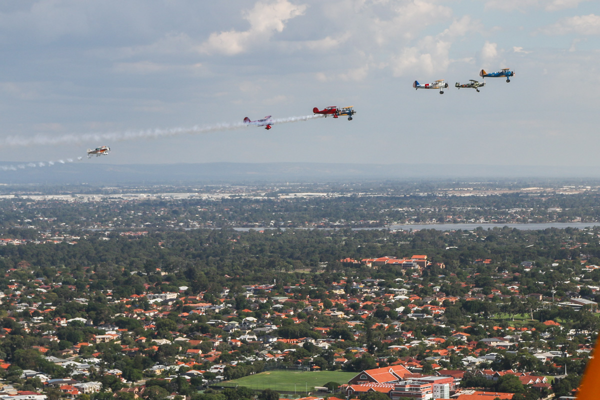 """Oldtimers formation, over South Perth - Tue 26 January 2016 - Australia Day Air Show. Aircraft in the formation are (L-R): VH-BQO Christen Eagle II (MSN V81), flown by Adam Gibbs; VH-YRB WACO Aircraft YMF-F5C, flown by Archie Dudgeon; VH-WQW Great Lakes 2T-1A-2 Sport Trainer, flown by Franc Smit; Boeing Stearmans VH-URC in US Army Air Corps markings, flown by Rod Edwards and VH-YND / """"42–755362 / 362"""" in US Navy markings, flown by Carl Ende; VH-KIL / """"14"""" CASA 1-131E Jungmann, in Japanese markings, flown by Bert Filippi; and Boeing Stearman VH-YDF / 4269 / 591, flown by Werner Buhlmann. Wesley College is visible at bottom right. Photo taken from VH-BTP / A17-744 De Havilland DH-82A Tiger Moth (MSN DHA1075/T315) owned by Clark Rees. Photo © David Eyre"""