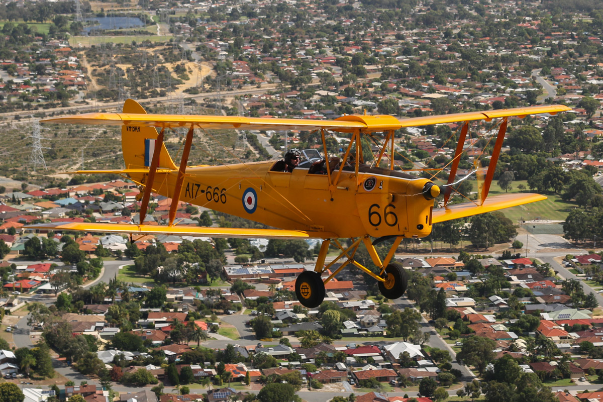 VH-BAR/A17-666 De Havilland DH-82A Tiger Moth (MSN DHA816/T342) owned and flown by Kevin Bailey, over Bibra Lake - Tue 26 January 2016 - Australia Day Air Show. Climbing to the northwest after departing Jandakot. Bibra Lake Primary School is visible under the left wing and Lakelands Reserve at upper left of photo. Photo taken from VH-BTP / A17-744 De Havilland DH-82A Tiger Moth (MSN DHA1075/T315) owned by Clark Rees. Photo © David Eyre
