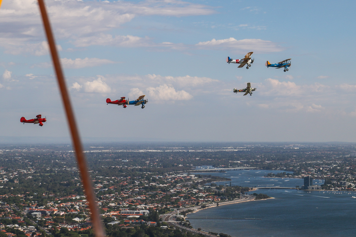 """Oldtimers formation, over South Perth - Tue 26 January 2016 - Australia Day Air Show. Aircraft in the formation are (L-R): VH-YRB WACO Aircraft YMF-F5C, flown by Archie Dudgeon; VH-WQW Great Lakes 2T-1A-2 Sport Trainer, flown by Franc Smit; Boeing Stearmans VH-URC in US Army Air Corps markings, flown by Rod Edwards and VH-YND / """"42–755362 / 362"""" in US Navy markings, flown by Carl Ende; VH-KIL / """"14"""" CASA 1-131E Jungmann, in Japanese markings, flown by Bert Filippi; and Boeing Stearman VH-YDF / 4269 / 591, flown by Werner Buhlmann. Canning River is visible in the distance. Photo taken from VH-BTP / A17-744 De Havilland DH-82A Tiger Moth (MSN DHA1075/T315) owned by Clark Rees. Photo © David Eyre"""
