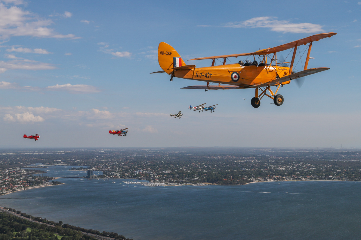 """VH-CKF/A17-421 De Havilland DH-82A Tiger Moth (MSN DHA596/T200), flown by Trevor Jones, with the Oldtimers formation in the background, over the Swan River near South Perth, Tue 26 January 2016 - Australia Day Air Show. Aircraft in the formation are (L-R): VH-YRB WACO Aircraft YMF-F5C, flown by Archie Dudgeon; VH-WQW Great Lakes 2T-1A-2 Sport Trainer, flown by Franc Smit; Boeing Stearman VH-URC in US Army Air Corps markings, flown by Rod Edwards; VH-KIL / """"14"""" CASA 1-131E Jungmann, in Japanese markings, flown by Bert Filippi; and Stearmans VH-YND / """"42–755362 / 362"""" in US Navy markings, flown by Carl Ende; and VH-YDF / 4269 / 591, flown by Werner Buhlmann. Canning River is visible on the left. Photo taken from VH-BTP / A17-744 De Havilland DH-82A Tiger Moth (MSN DHA1075/T315) owned by Clark Rees. Photo © David Eyre"""