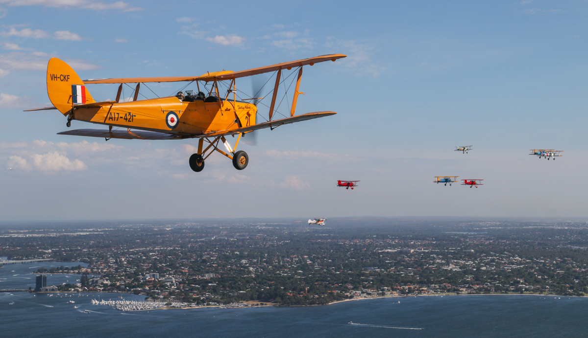 """VH-CKF/A17-421 De Havilland DH-82A Tiger Moth (MSN DHA596/T200), flown by Trevor Jones, with the Oldtimers formation in the background, over the Swan River near South Perth, Tue 26 January 2016 - Australia Day Air Show. Oldtimers formation, over South Perth - Tue 26 January 2016 - Australia Day Air Show. Aircraft in the formation are (L-R): VH-BQO Christen Eagle II (MSN V81), flown by Adam Gibbs; VH-YRB WACO Aircraft YMF-F5C, flown by Archie Dudgeon; Boeing Stearman VH-URC in US Army Air Corps markings, flown by Rod Edwards; VH-WQW Great Lakes 2T-1A-2 Sport Trainer, flown by Franc Smit; VH-KIL / """"14"""" CASA 1-131E Jungmann, in Japanese markings, flown by Bert Filippi; and Stearmans VH-YND / """"42–755362 / 362"""" in US Navy markings, flown by Carl Ende; and VH-YDF / 4269 / 591, flown by Werner Buhlmann. Canning River is visible on the left. Photo taken from VH-BTP / A17-744 De Havilland DH-82A Tiger Moth (MSN DHA1075/T315) owned by Clark Rees. Photo © David Eyre"""