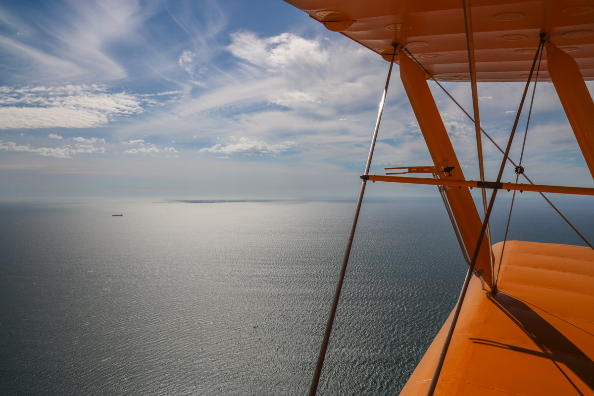 Indian Ocean and Rottnest Island, seen from VH-BTP / A17-744 De Havilland DH-82A Tiger Moth (MSN DHA1075/T315) flown by Clark Rees, over Mosman Park, Tue 26 January 2016 - Australia Day Air Show. The small speck at bottom centre is Tiger Moth VH-BAR/A17-666 (MSN DHA816/T342) flown by Kevin Bailey. Photo © David Eyre