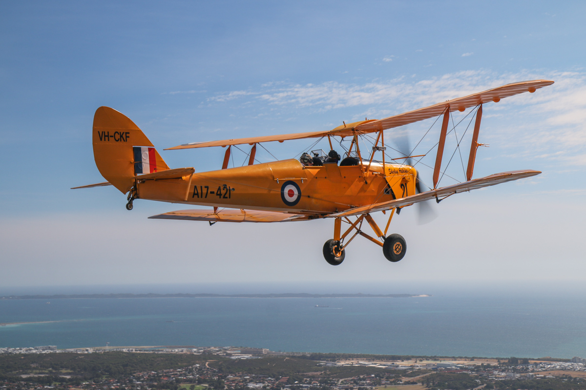 VH-CKF/A17-421 De Havilland DH-82A Tiger Moth (MSN DHA596/T200) owned by the Royal Aero Club of Western Australia Inc, flown by Trevor Jones, over Kardinya - Tue 26 January 2016 - Australia Day Air Show. Visible in the distance are North Coogee and Garden Island. Photo taken from VH-BTP / A17-744 De Havilland DH-82A Tiger Moth (MSN DHA1075/T315) owned by Clark Rees Photo © David Eyre