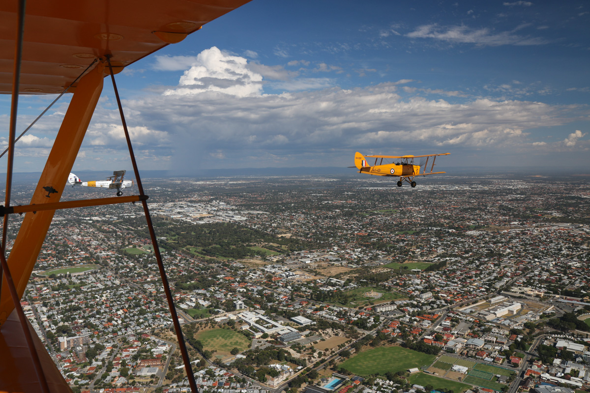 De Havilland DH-82A Tiger Moths VH-NOV (MSN DHA1088) flown by Barry Markham; and VH-CKF/A17-421 (MSN DHA596/T200), flown by Trevor Jones, over Fremantle, Tue 26 January 2016 - Australia Day Air Show. At lower right are the cream-coloured buildings of Fremantle Prison, now a tourist attraction. Photo taken from VH-BTP / A17-744 De Havilland DH-82A Tiger Moth (MSN DHA1075/T315) flown by Clark Rees. Photo © David Eyre