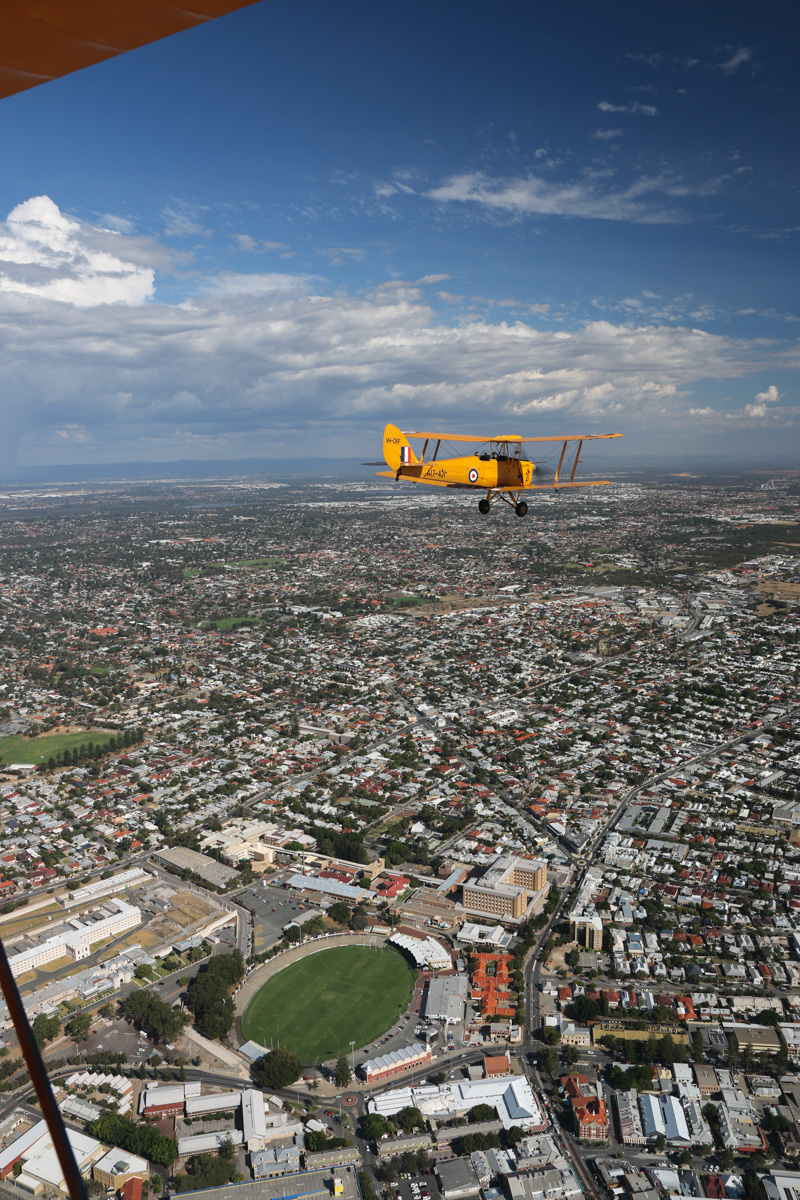 VH-CKF/A17-421 De Havilland DH-82A Tiger Moth (MSN DHA596/T200), flown by Trevor Jones, over Fremantle, Tue 26 January 2016 - Australia Day Air Show. Heading south, on the way back to Jandakot. At lower left are the cream-coloured buildings of Fremantle Prison, now a tourist attraction, Fremantle Oval just to the right with the markets and hospital nearby. Photo taken from VH-BTP / A17-744 De Havilland DH-82A Tiger Moth (MSN DHA1075/T315) flown by Clark Rees. Photo © David Eyre