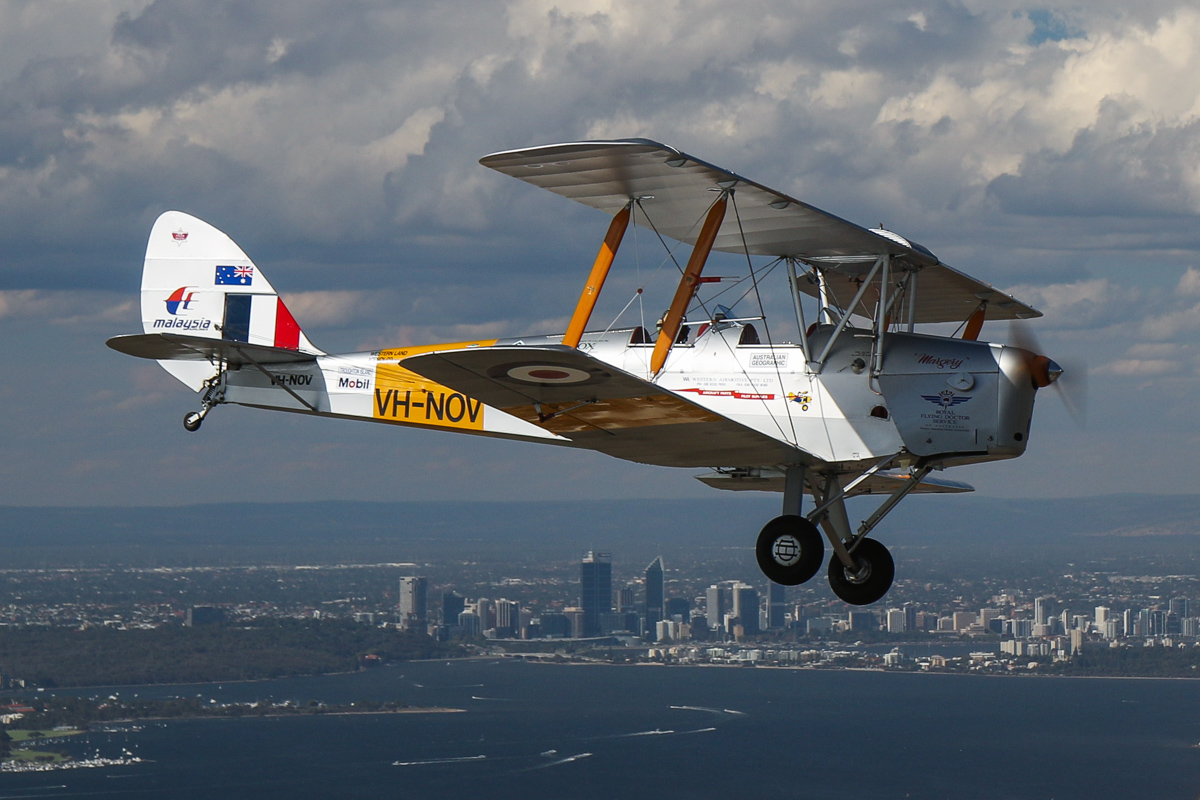 VH-NOV De Havilland DH-82A Tiger Moth (MSN DHA1088) flown by Barry Markham with Perth city behind, Tue 26 January 2016 - Australia Day Air Show. This aircraft was built by De Havilland Aircraft at Bankstown, NSW in 1945, and was delivered to the RAAF as A17-757. It was sold in 1956 and became VH-RNQ with Royal Newcastle Aero Club, Broadmeadow, NSW, but was damaged in 1959 and sold for spares. Barry Markham restored the aircraft in 1991 as VH-NOV and in 1998, set a number of records when he flew it from Perth to London, to raise funds for the RFDS. Photo taken from VH-BTP / A17-744 De Havilland DH-82A Tiger Moth (MSN DHA1075/T315) flown by Clark Rees, whilst we flew over North Coogee, near Fremantle. Photo © David Eyre