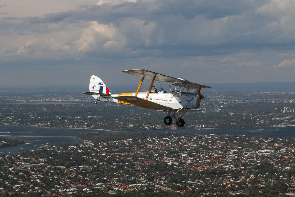 VH-NOV De Havilland DH-82A Tiger Moth (MSN DHA1088) flown by Barry Markham with Point Walter in Bicton behind, Tue 26 January 2016 - Australia Day Air Show. This aircraft was built by De Havilland Aircraft at Bankstown, NSW in 1945, and was delivered to the RAAF as A17-757. It was sold in 1956 and became VH-RNQ with Royal Newcastle Aero Club, Broadmeadow, NSW, but was damaged in 1959 and sold for spares. Barry Markham restored the aircraft in 1991 as VH-NOV and in 1998, set a number of records when he flew it from Perth to London, to raise funds for the RFDS. Photo taken from VH-BTP / A17-744 De Havilland DH-82A Tiger Moth (MSN DHA1075/T315) flown by Clark Rees, whilst we flew over Hamilton Hill. Photo © David Eyre
