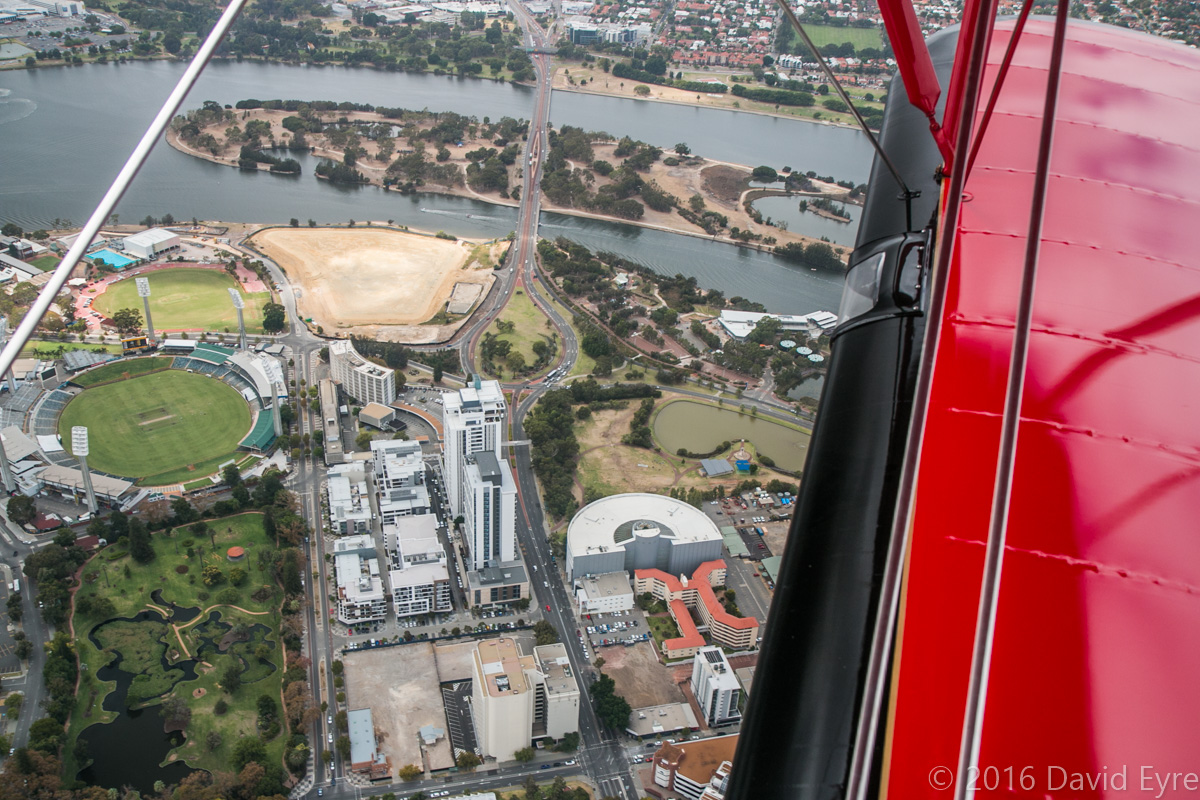 View facing southeast of East Perth and Heirisson Island, seen from VH-YRB WACO Aircraft YMF-F5C (MSN F5C105), owned by Archie Dudgeon, heading northeast over East Perth - Sun 28 February 2016. Visible in this view are Queens Gardens at lower left corner, with the WACA cricket ground next to it (centre left), and Adelaide Terrace and the Causeway crossing Heirisson Island. Photo © David Eyre