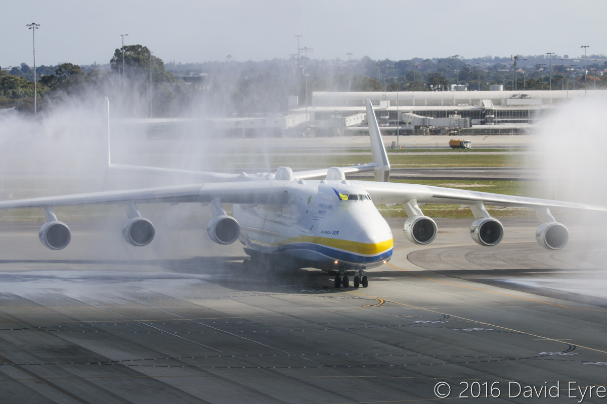 UR-82060 Antonov An-225 Mriya (MSN 19530503763/01-01) of Antonov Airlines (Antonov Design Bureau) at Perth Airport - Sun 15 May 2016. First visit by the An-225 to Australia. Landed on runway 21 at 11:52AM from Kuala Lumpur as ADB3610, carrying a 117-tonne Brush generator from Prague, for Worsley Alumina Refinery. It continued to the end of the runway and is seen here at 12:05PM, receiving a water cannon salute from airport fire crews as it slowly taxied to Bay 162, opposite the International Terminal. Photo © David Eyre