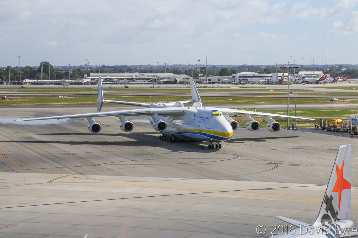 UR-82060 Antonov An-225 Mriya (MSN 19530503763/01-01) of Antonov Airlines (Antonov Design Bureau) at Perth Airport - Sun 15 May 2016. First visit by the An-225 to Australia. Landed on runway 21 at 11:52AM from Kuala Lumpur as ADB3610, carrying a 117-tonne Brush generator from Prague, for Worsley Alumina Refinery. Seen here at 12:06PM, after receiving a water cannon salute from airport fire crews as it slowly taxied to Bay 162, opposite the International Terminal. Co-pilot flying the Ukrainian flag from the cockpit. Photo © David Eyre