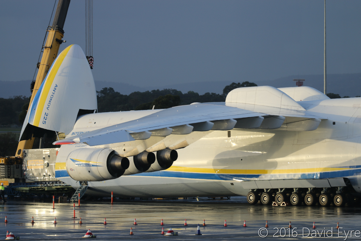 UR-82060 Antonov An-225 Mriya (MSN 19530503763/01-01) of Antonov Airlines (Antonov Design Bureau) at Perth Airport - Sun 15 May 2016. First visit by the An-225 to Australia. Seen here at 4:58PM, parked at Bay 162, with the 117-tonne Brush generator emerging, with two cranes getting ready for unloading it onto a truck. Photo © David Eyre