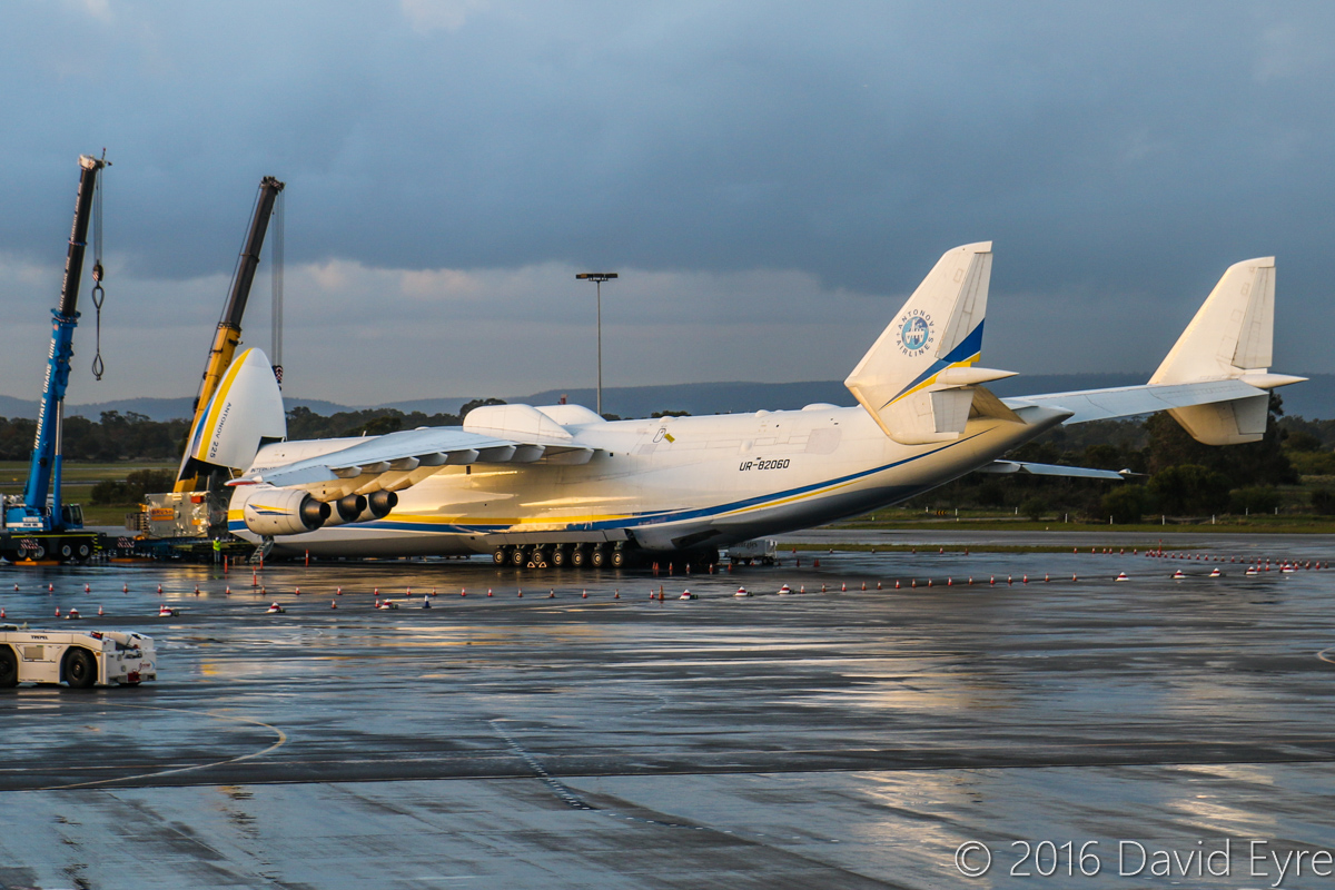 UR-82060 Antonov An-225 Mriya (MSN 19530503763/01-01) of Antonov Airlines (Antonov Design Bureau) at Perth Airport - Sun 15 May 2016. First visit by the An-225 to Australia. Seen here at 5:05PM, parked at Bay 162, with the 117-tonne Brush generator emerging, with two cranes getting ready for unloading it onto a truck. Photo © David Eyre