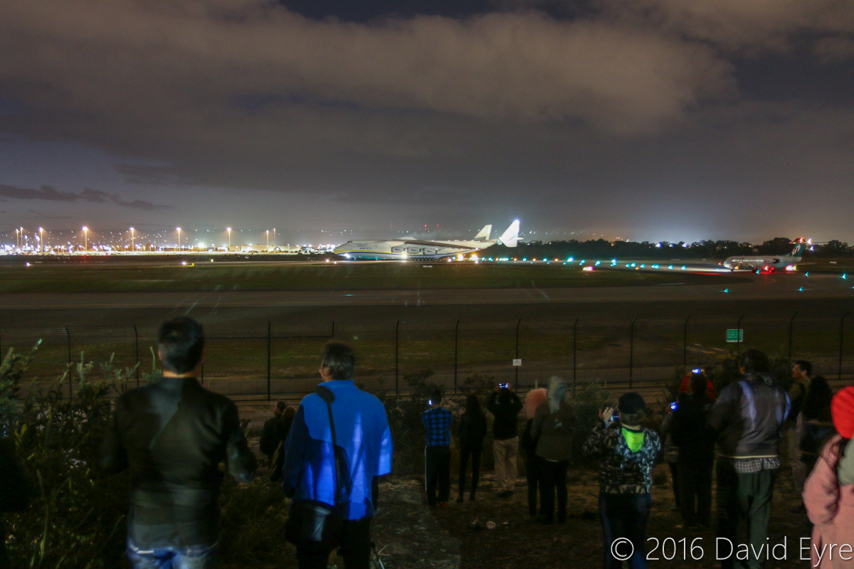 Spectators watching UR-82060 Antonov An-225 Mriya (MSN 19530503763/01-01) of Antonov Airlines (Antonov Design Bureau) from the Public Viewing Area on Dunreath Drive, at Perth Airport - Tue 17 May 2016. First visit by the An-225 to Australia. Seen here at 5:57AM, as the aircraft ran-up its engines on runway 03, prior to taking off at 5:59AM as ADB3655 direct to Dubai World Centre. A Fokker 100 of Network Aviation is waiting to line up for take off to the right of the photo. Photo © David Eyre