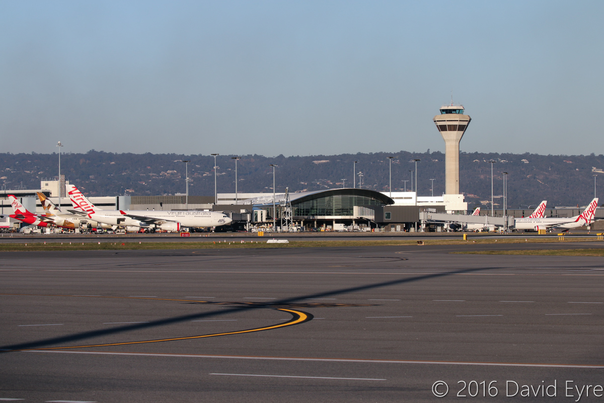 Terminal 1 Domestic and control towerat Perth Airport – Thu 2 June 2016. Photo taken at 4:30pm. Left to right: 9M-XXZ Airbus A330-343X (MSN 1612) of AirAsia X, named 'Son of Xcalibur', parked at Bay 151 - departed as D7233 to Kuala Lumpur at 5:06pm. A6-BLG Boeing 787-9 Dreamliner (MSN 39652/432) of Etihad is parked at Bay 150 and was on its first visit to Perth - it was only delivered on 26 May 2016 and was making the first official Etihad 787 service to Perth (an unplanned visit occurred on 30 May 2016). Departed as EY487 to Abu Dhabi at 5:16pm. VH-XFC Airbus A330-243 (MSN 1293) of Virgin Australia, named 'Mooloolabah Beach' is parked at Bay 148 at Terminal 1 Domestic - it departed at 5:45pm as VA694 to Melbourne. VH-YVC Boeing 737-8FE (MSN 40997/3832), named 'Jetty Beach' of Virgin Australia, parked at Bay 147 at Terminal 1 Domestic - arrived at 3:44pm as VA466 from Brisbane, departed back as VA471 at 5:26pm. Photo © David Eyre