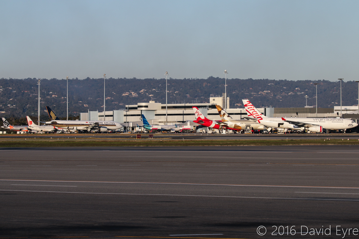 Terminal 1 at Perth Airport – Thu 2 June 2016. Photo taken at 4:34pm. Left to right: VH-VGP Airbus A320-232 (MSN 4343) of Jetstar, parked at Bay 155 - arrived at 3:28pm as JQ109 from Denpasar (Bali), departed back there at 6:05pm as JQ116. 9M-LNW Boeing 737-8GP (MSN 39875/5616) of Malindo Air, parked at Bay 154 - arrived at 4:02pm as OD151 from Kuala Lumpur, departed back as OD152 at 5:28pm. 9V-SQN Boeing 777-212ER (MSN 33373/487) of Singapore Airlines, parked at Bay 153 - arrived at 2:21pm as SQ223 from Singapore, departed back as SQ214 at 5:23pm. PK-GNU Boeing 737-8U3 (MSN 41812/5613) of Garuda Indonesia, parked at Bay 152 - arrived at 4:16pm as GA724 from Jakarta, departed back as GA725 at 6:53pm. 9M-XXZ Airbus A330-343X (MSN 1612) of AirAsia X, named 'Son of Xcalibur', parked at Bay 151 - departed as D7233 to Kuala Lumpur at 5:06pm. A6-BLG Boeing 787-9 Dreamliner (MSN 39652/432) of Etihad is parked at Bay 150 and was on its first visit to Perth - it was only delivered on 26 May 2016 and was making the first official Etihad 787 service to Perth (an unplanned visit occurred on 30 May 2016). Departed as EY487 to Abu Dhabi at 5:16pm. VH-XFC Airbus A330-243 (MSN 1293) of Virgin Australia, named 'Mooloolabah Beach' is parked at Bay 149 at Terminal 1 Domestic - it departed at 5:45pm as VA694 to Melbourne. Photo © David Eyre